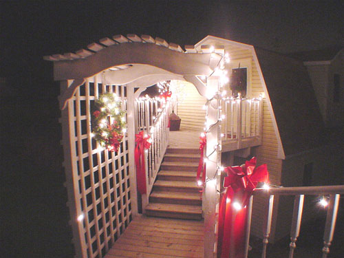 A late-night holiday-lit trellis walkway